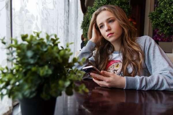 Грустная девушка с мобильным в руках
